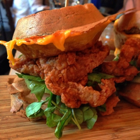 Fried Chicken & Waffle Sandwich, Cheddar Cheese, Pickled Green Tomato, Watercress, Whiskey Maple Syrup
